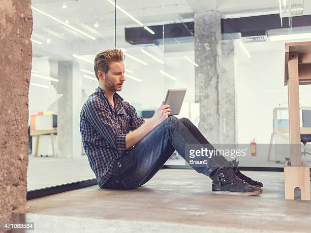 Young ginger man sitting on floor and using digital tablet.