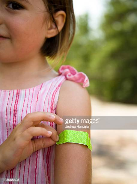 Young girl, 3 years old, with green band-aid on arm