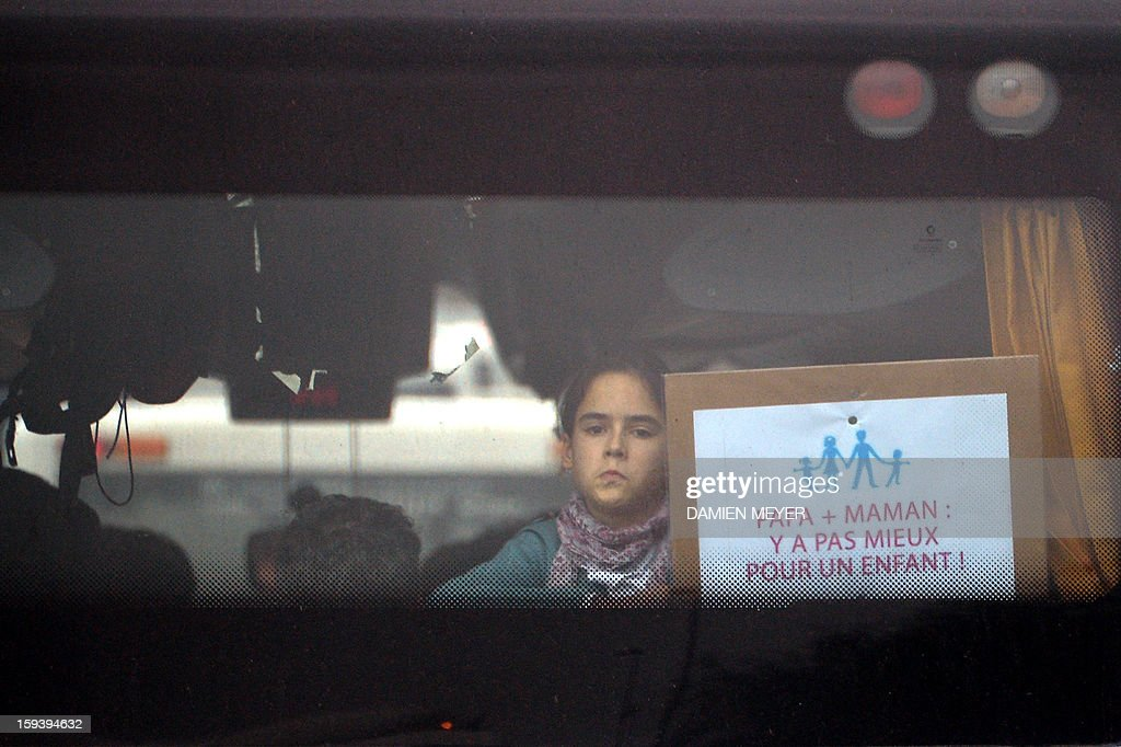 A young girl aboard a bus holds a placard reading 'Dad + Mom is the best for a child', in the morning on January 13, 2013, in Avranches, in western France, en route to attend Paris' demonstration against same-sex wedding. Tens of thousands are set to march in Paris on January 13 to denounce government plans to legalise same-sex marriage and adoption, which have angered many Catholics and of the right-wing opposition. Placard at center reads : ''All born of a man and a woman.'