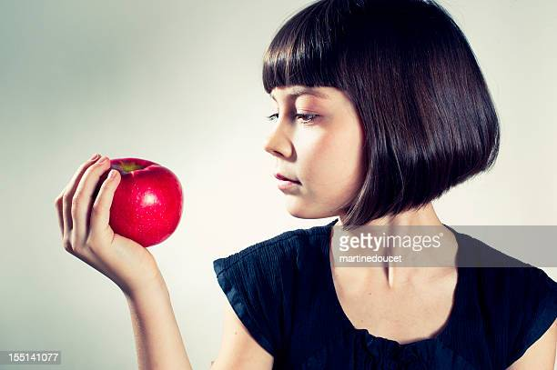 Young girl about to eat a red apple.