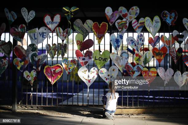 A young girl adds finishing touches to paper hearts adorning a fence in Kensington near the burntout remains of Grenfell Tower in London on August 25...