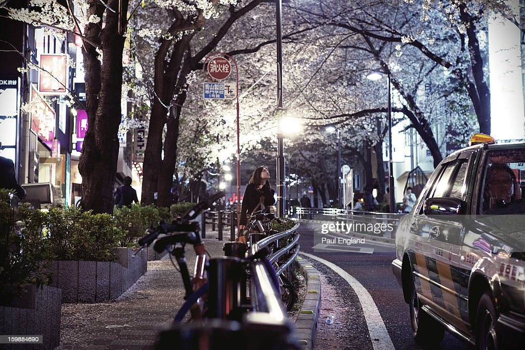 CONTENT] A young girl admires the Cherry Blossoms at night, in Shibuya's Sakuragaokacho.