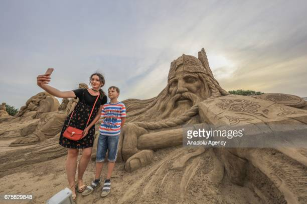 A young girl and a boy take a selfie with Thor Greek mythological character that exhibited during the 11th International Antalya Sand Sculpture...