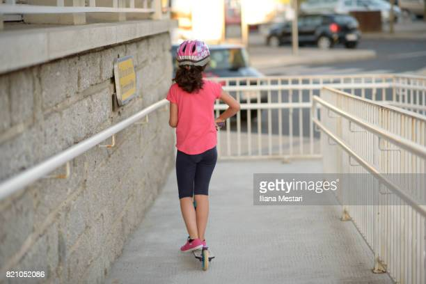 A young girl and a scooter on a walkway
