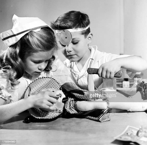 A young girl and a young boy play doctor and operate on dolls 1948
