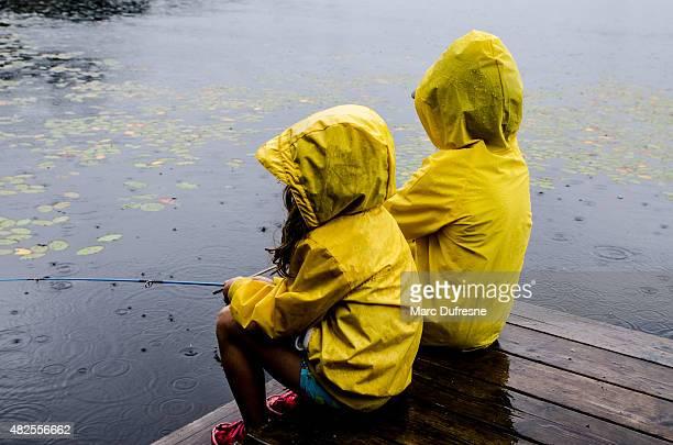 Young girl and boy la pesca con lluvia