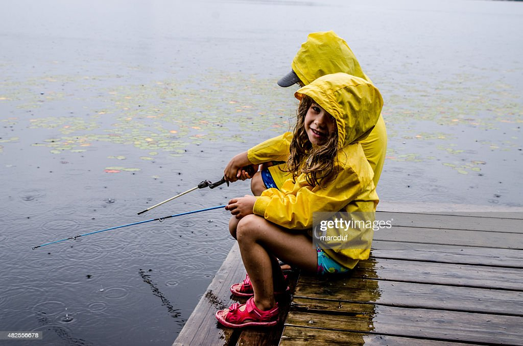 Young girl and boy fishing under rain : Stock Photo