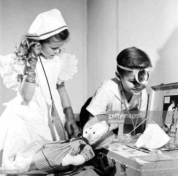 A young girl and boy play doctor with dolls 1948
