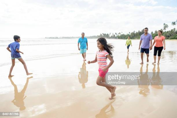 Young girl and boy playing on beach with family