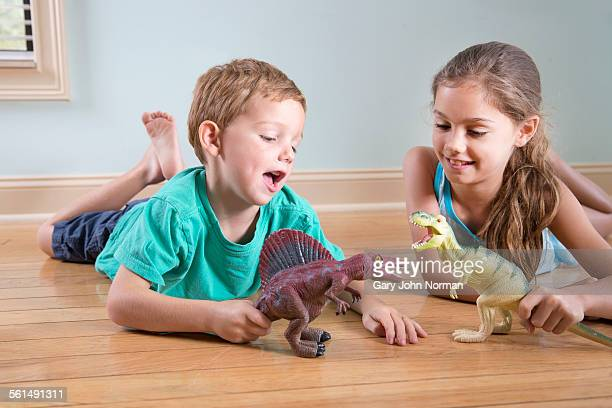 Young girl and boy playing with toy dinosaurs.