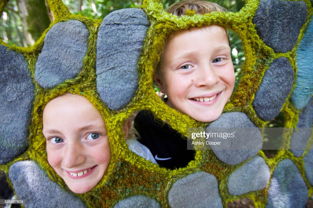 A young girl and boy poke there faces into a hole in a textile design by Dianne Standen