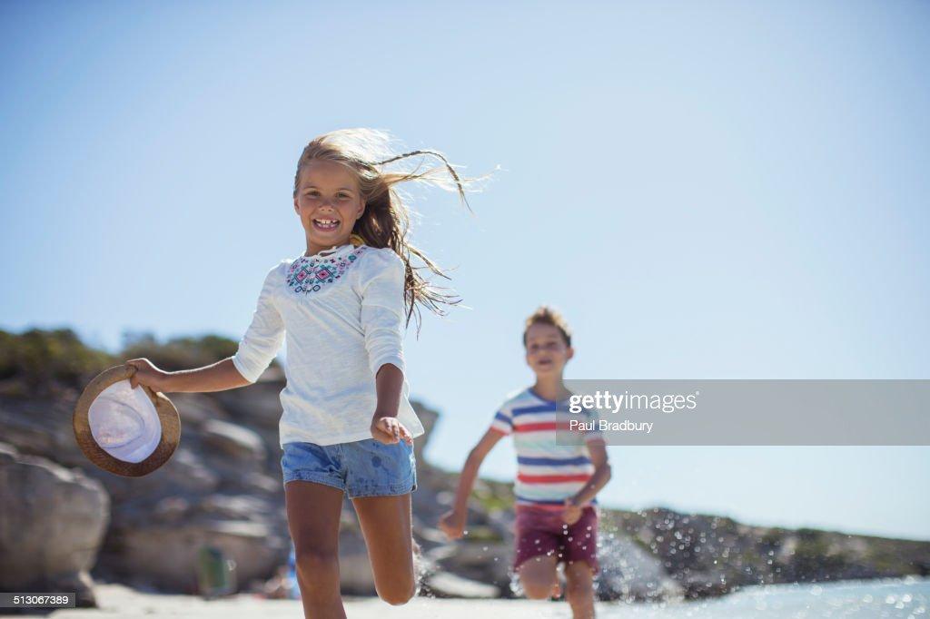Young girl and boy running along beach