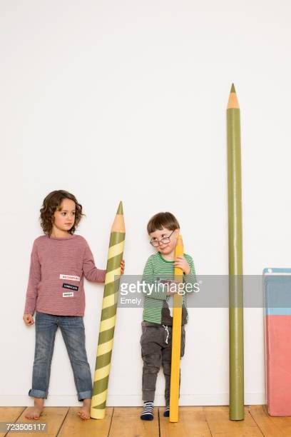Young girl and boy standing, holding giant size pencils, giant stationery leaning on wall beside him
