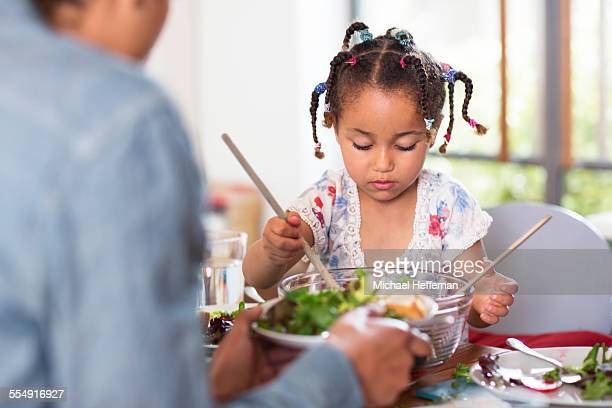Young girl and father with salad bowl