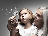 Young girl and grandmother blowing dandelion seeds