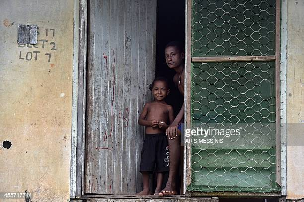 A young girl and her brother look on while standing at the door of their house in the town of Kerema Papua New Guinea on September 7 2014 AFP PHOTO /...