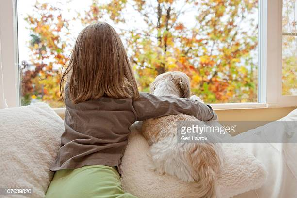 Young girl and her dog looking out the window