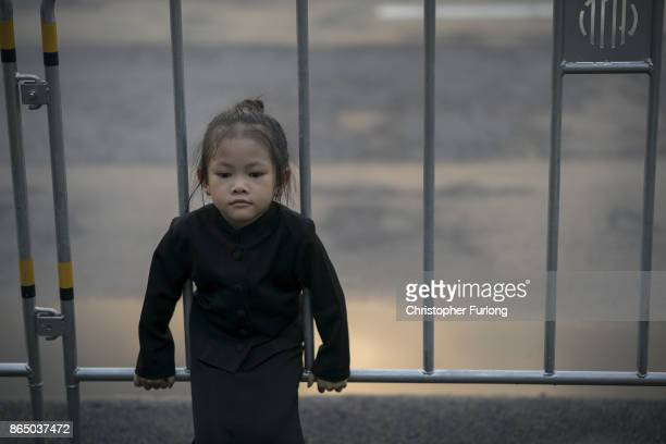A young girl and her family gather to pay their respects to Thailand's late King Bhumibol Adulyadej as the city prepares for his cremation on October...