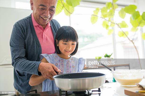 Young girl and her grandfather cooking together