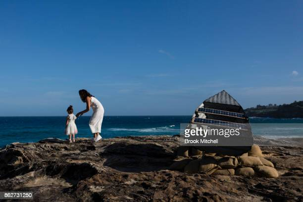 A young girl and her mother are pictured at the work 'Les St Hill and the Tin Canoe' by John Blay Amanda Stuart and Jane Ulman at Sculpture By The...