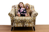 Young girl and her puppy relaxing in an armchair together both sticking out their tongues as she mimics the dog panting