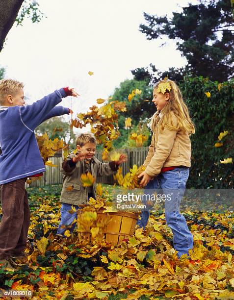 Young Girl and Her Two Brothers Stand in Their Garden Throwing Autumn Leaves From a Basket