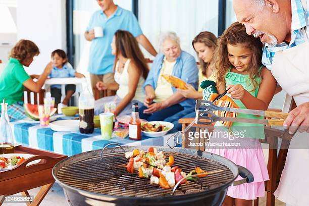 Young girl and older man grilling at barbecue