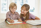 Young girl and young boy doing homework at kitchen table