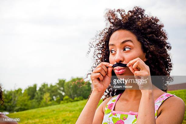 A young girl applying a fake mustache.