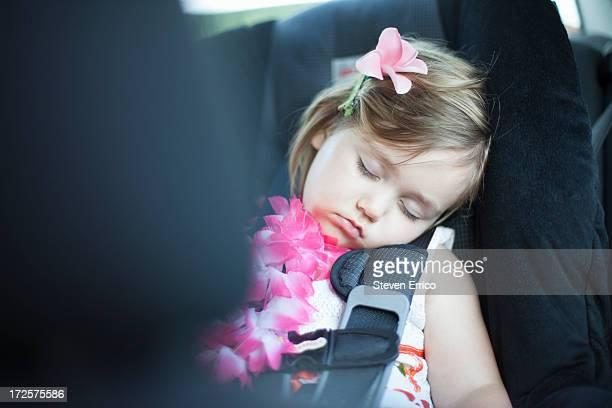 Young girl asleep in car seat