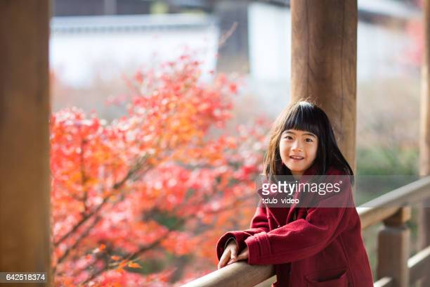Young girl at a temple enjoying autumn leaves