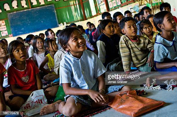 A young girl at an NGO school laughs when the teacher tells the class how to practice safe sex