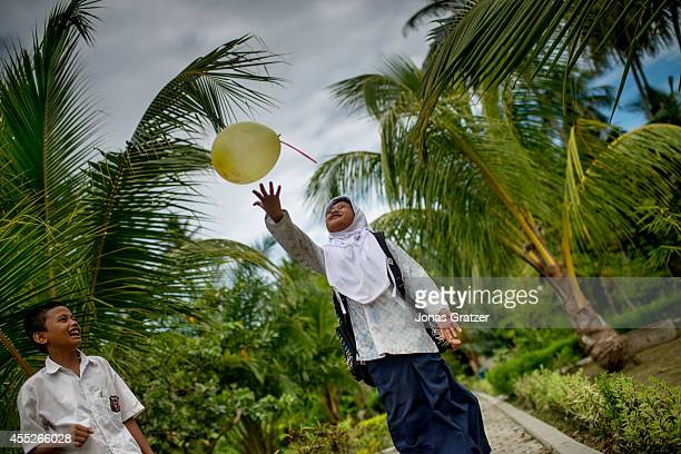 A young girl at an orphanage playing with a balloon after school she lost most of her family to the tsunami disaster of the 2004 winter and has grown...