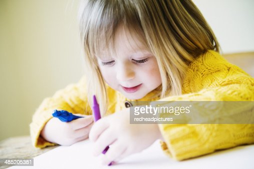 Young girl at kitchen table coloring in with felt pens