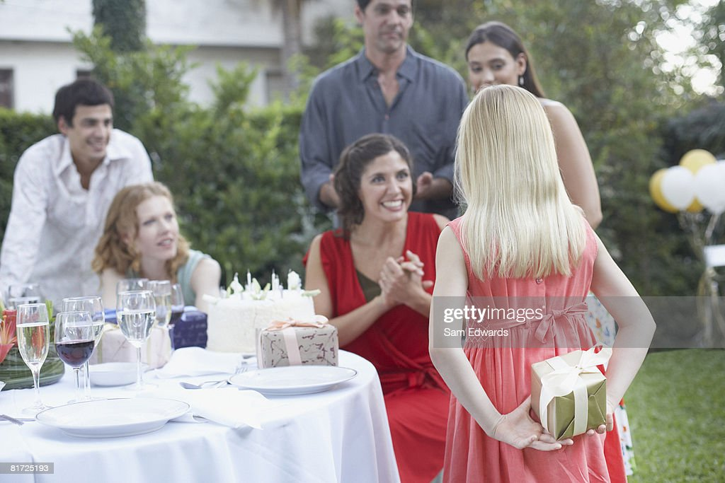 Young girl at outdoor birthday party about to give gift to woman with partygoers watching and smiling : Stock Photo