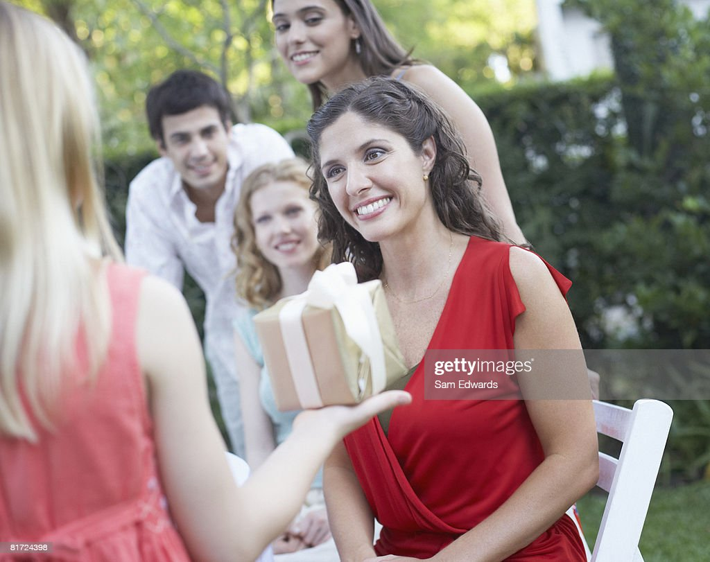 Young girl at outdoor party giving gift to woman with partygoers watching and smiling : Stock Photo