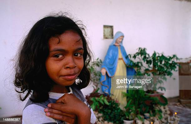 Young girl at the makeshift altar in a burnt out church in Dili.