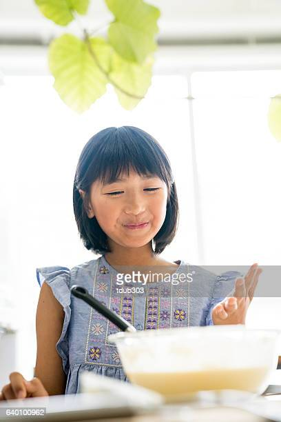 Young girl baking a cake all by herself