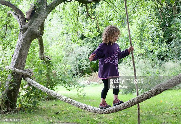 young girl balancing on a rope in the garden