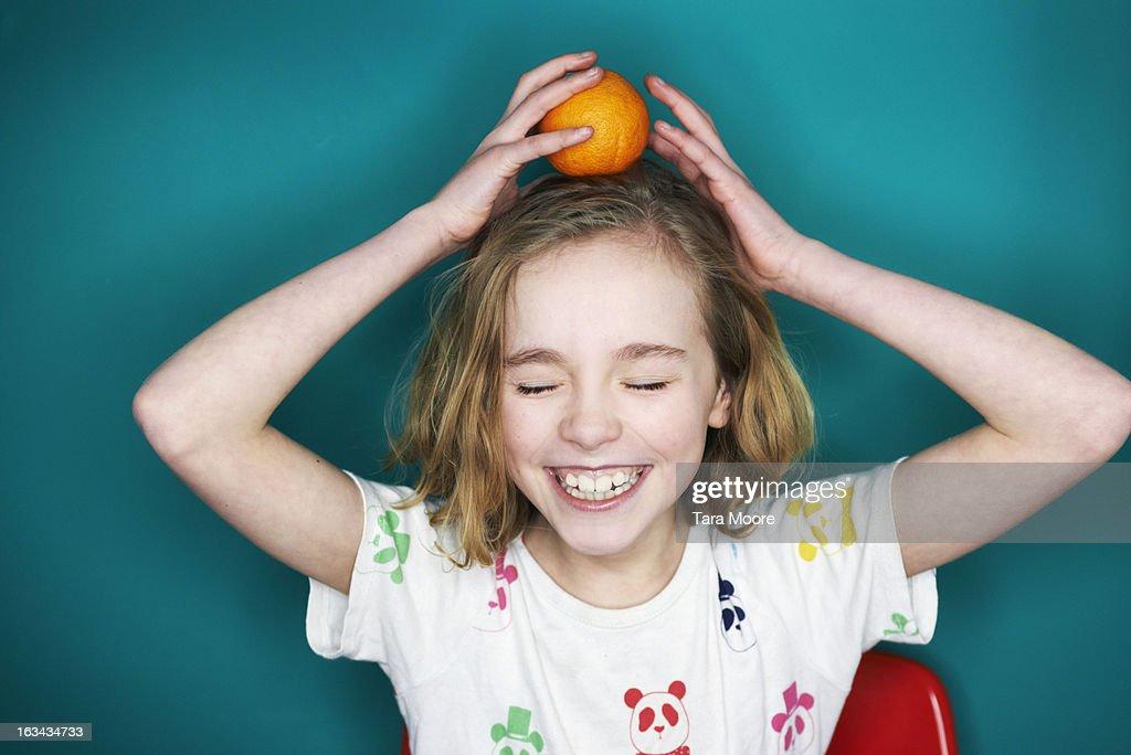 young girl balancing orange on head : Stock Photo