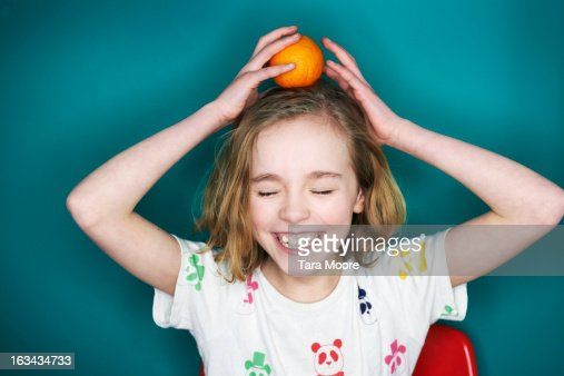 young girl balancing orange on head : Stock Photo