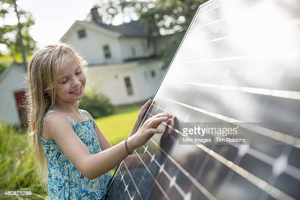 A young girl beside a large solar panel in a farmhouse garden.