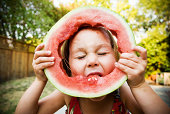 A young girl blissfully eating watermelon