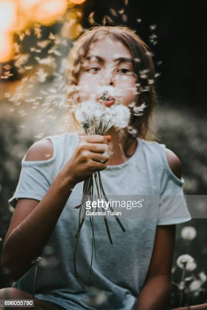 Young girl blowing a dandelion at sunset