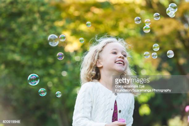 Young girl blowing bubbles in backyard