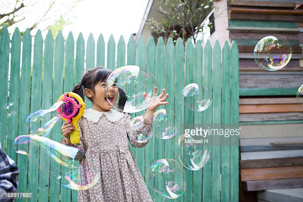 Young girl  blowing bubbles outdoor