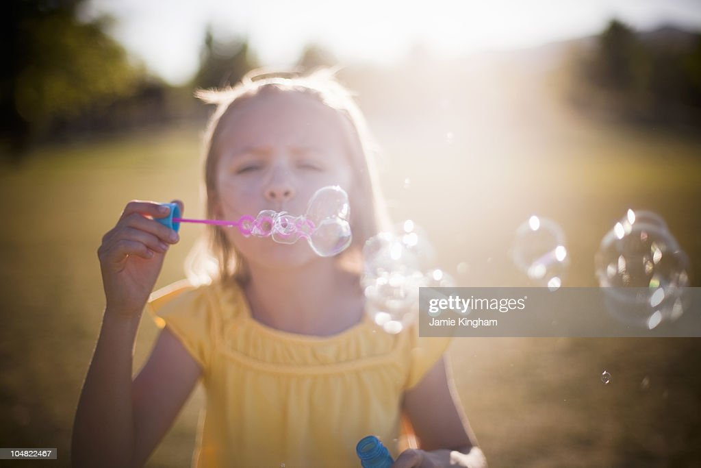 Young girl blowing bubbles : Stock Photo