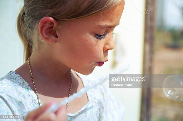Young girl blowing bubbles.