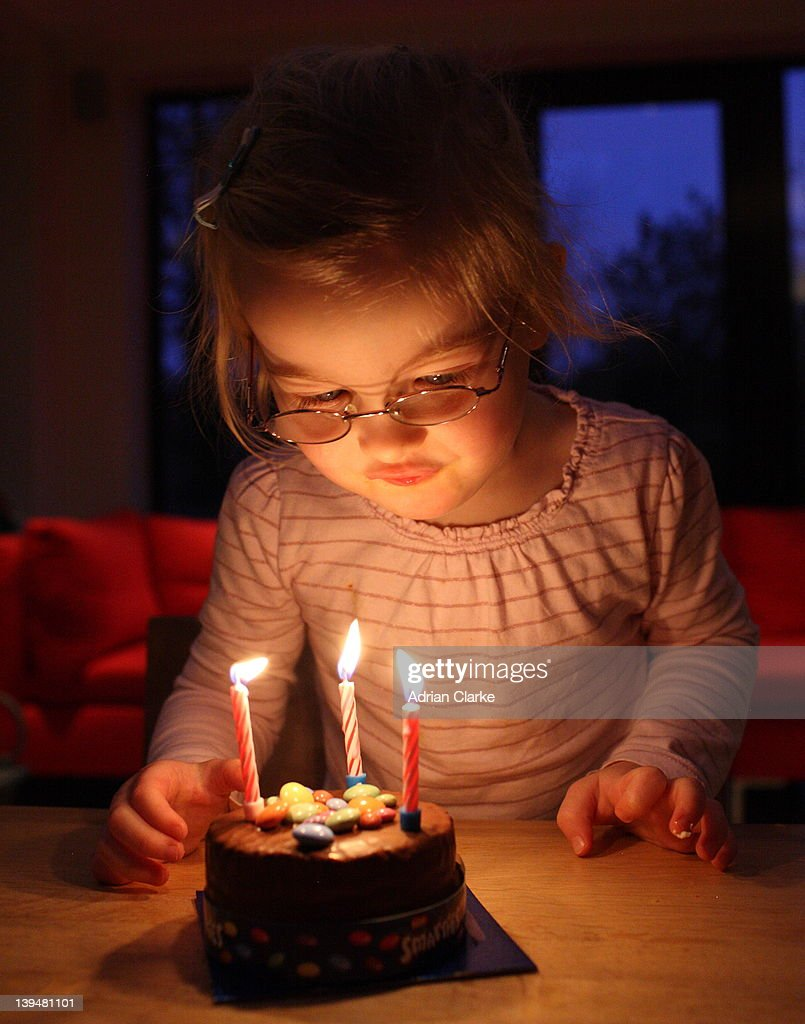 Young girl blowing candles : Stock Photo