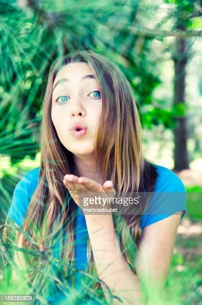 Giovane ragazza soffiare baci da pinewood.